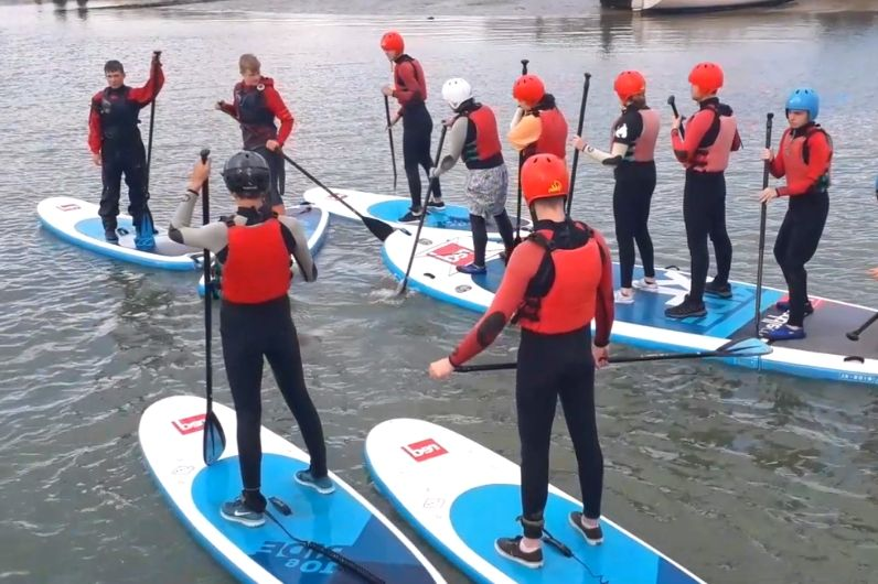 A group of watersports participants on paddleboards