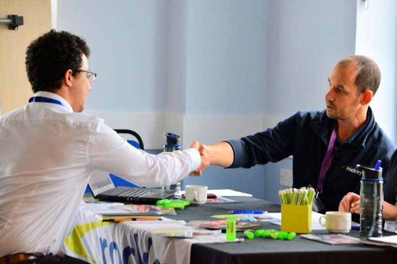A student shaking hands with a recruitment officer