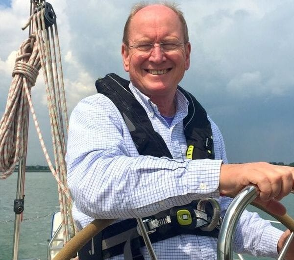 A man smiling as he navigates his yacht