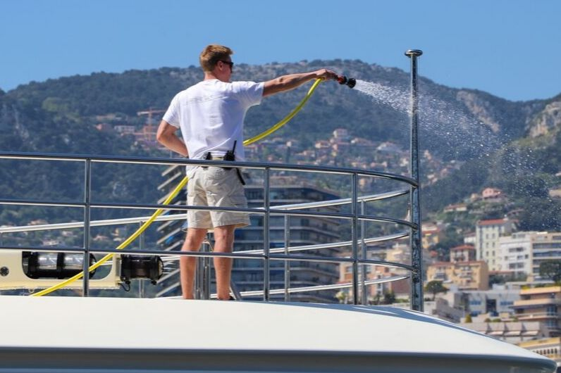 A superyacht deck crew officer washing the boat