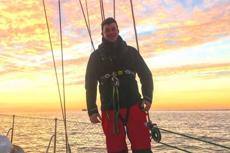 A young man standing onboard a yacht