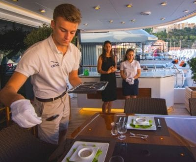 A male Hospitality student setting a table onboard a Superyacht