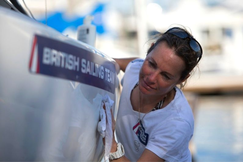 Ambassador Helena Lucas wiping down side of boat