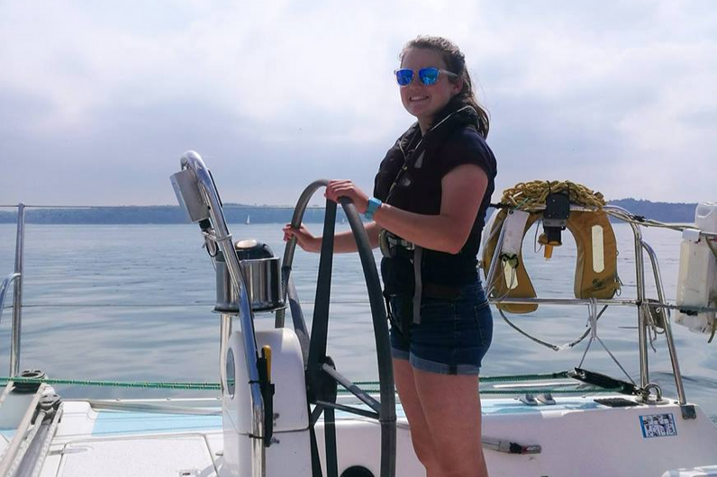 A young female sailor at the helm of a yacht