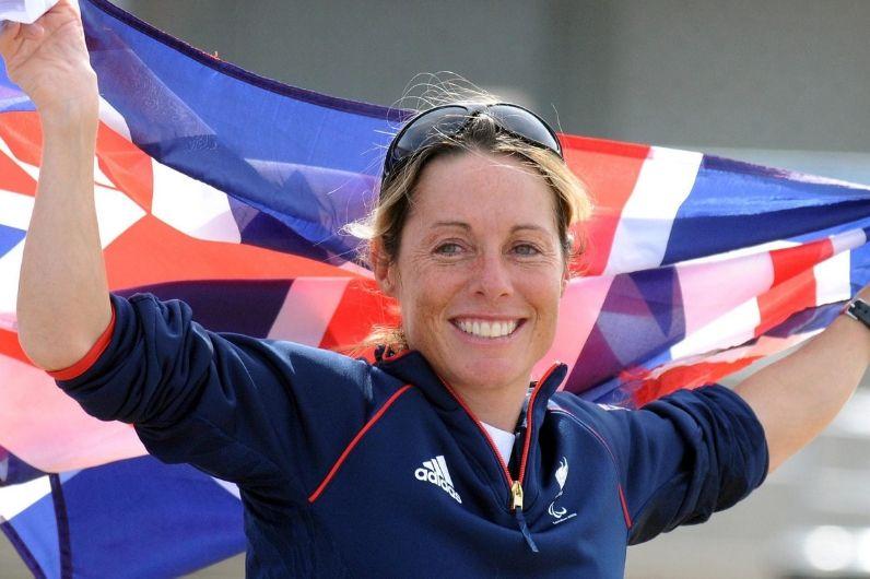 Ambassador Helena Lucas holding Union Jack flag