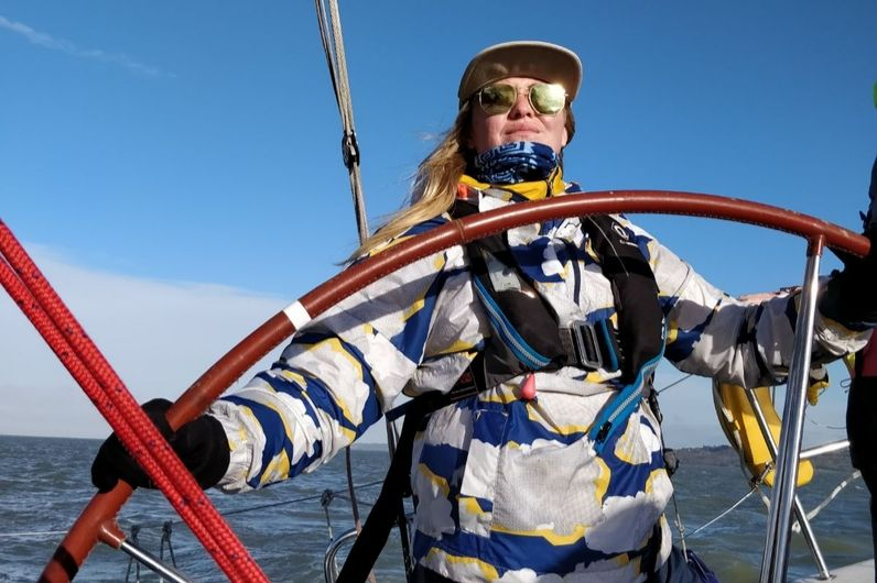 A young female sailor navigating a yacht