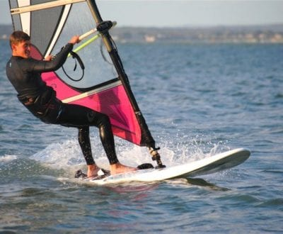 A young man windsurfing on the Solent waters