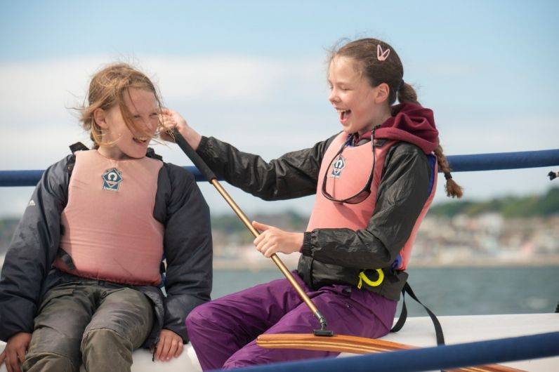 Two young females having fun whilst navigating a keel boat