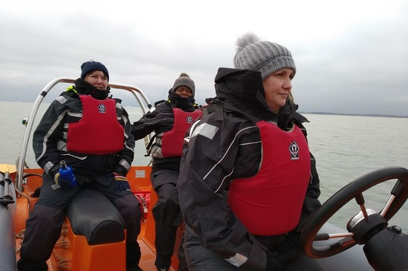 Adults on board a powerboat with life jackets