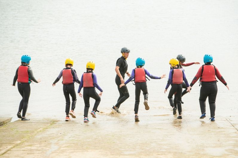 Students running from the slipway into the water