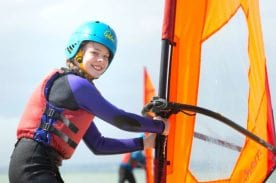 A female student holding up her Windsurf sail