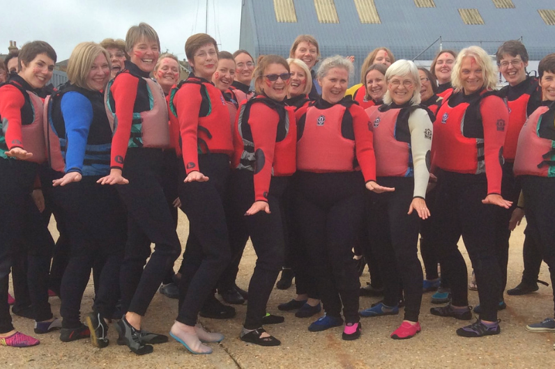 A group shot of older ladies participating in a watersports activity