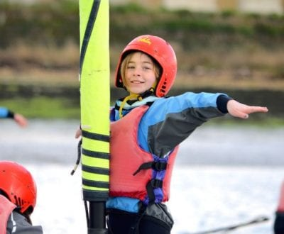 Child standing up on a boat against the sail pole