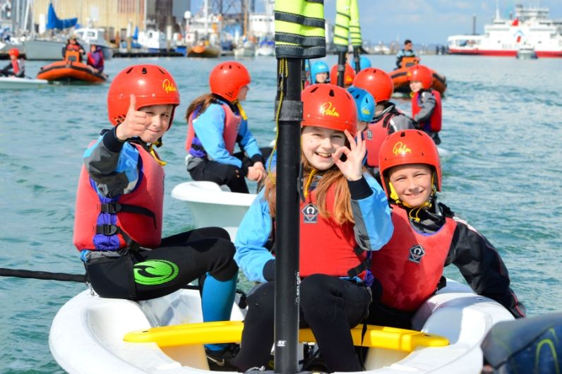 Young children smiling and putting their thumbs up on a sail boat