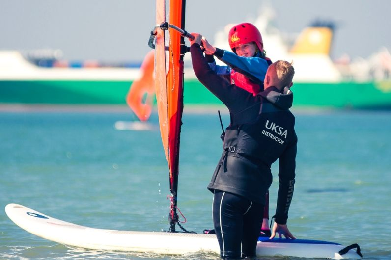 A student receiving guidance from an instructor on how to windsurf