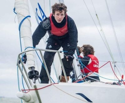 Sean Starkey on the bow of a yacht whilst training