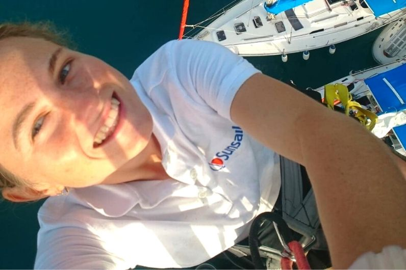Pip Grundy up the mast of a yacht whilst wearing safety equipment