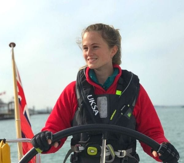 Pip Grundy smiling whilst navigating a yacht