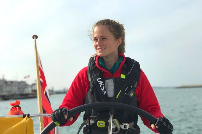 Professional Yachtmaster Pip Grundy smiling whilst navigating a yacht