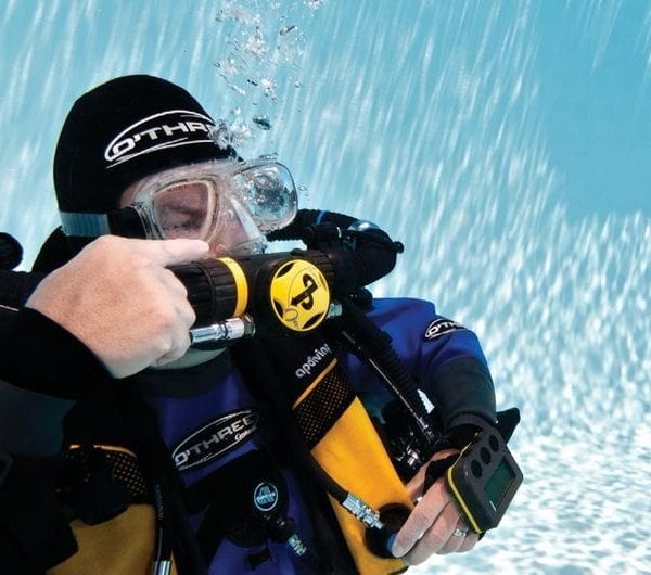 A diver pointing at his breathing equipment in a swimming pool
