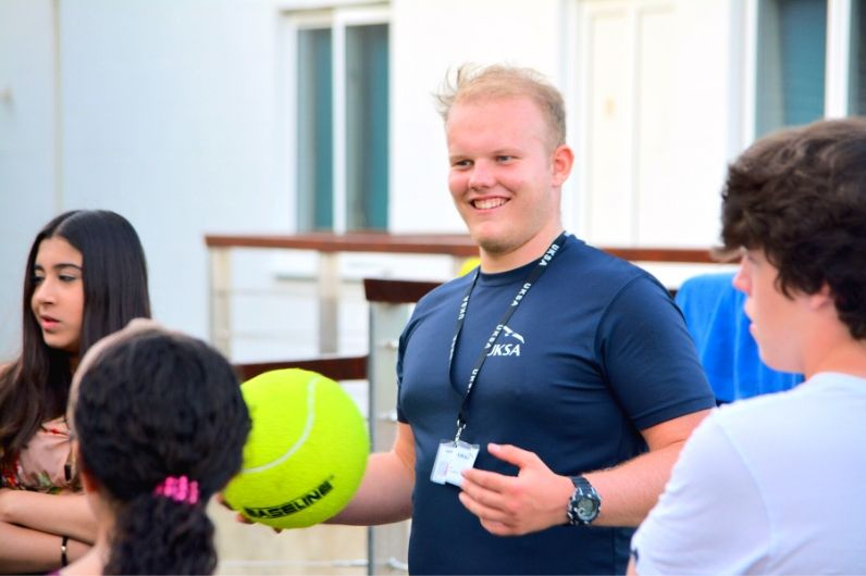 A UKSA instructor smiling and holding a ball