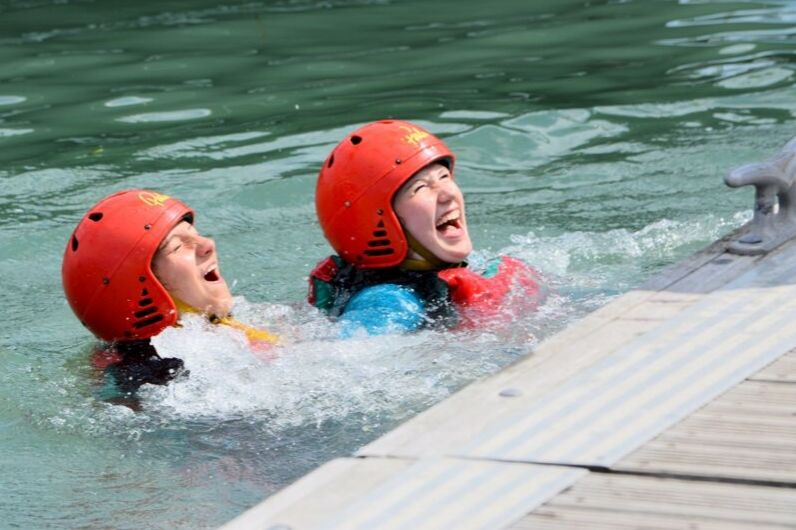 Two students in the water wearing red helmets