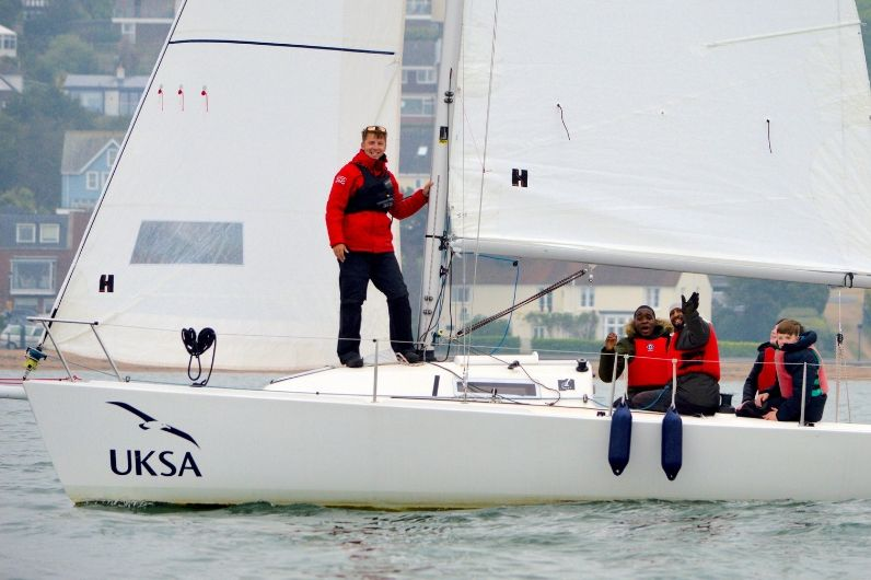 Students waving and smiling on a yacht