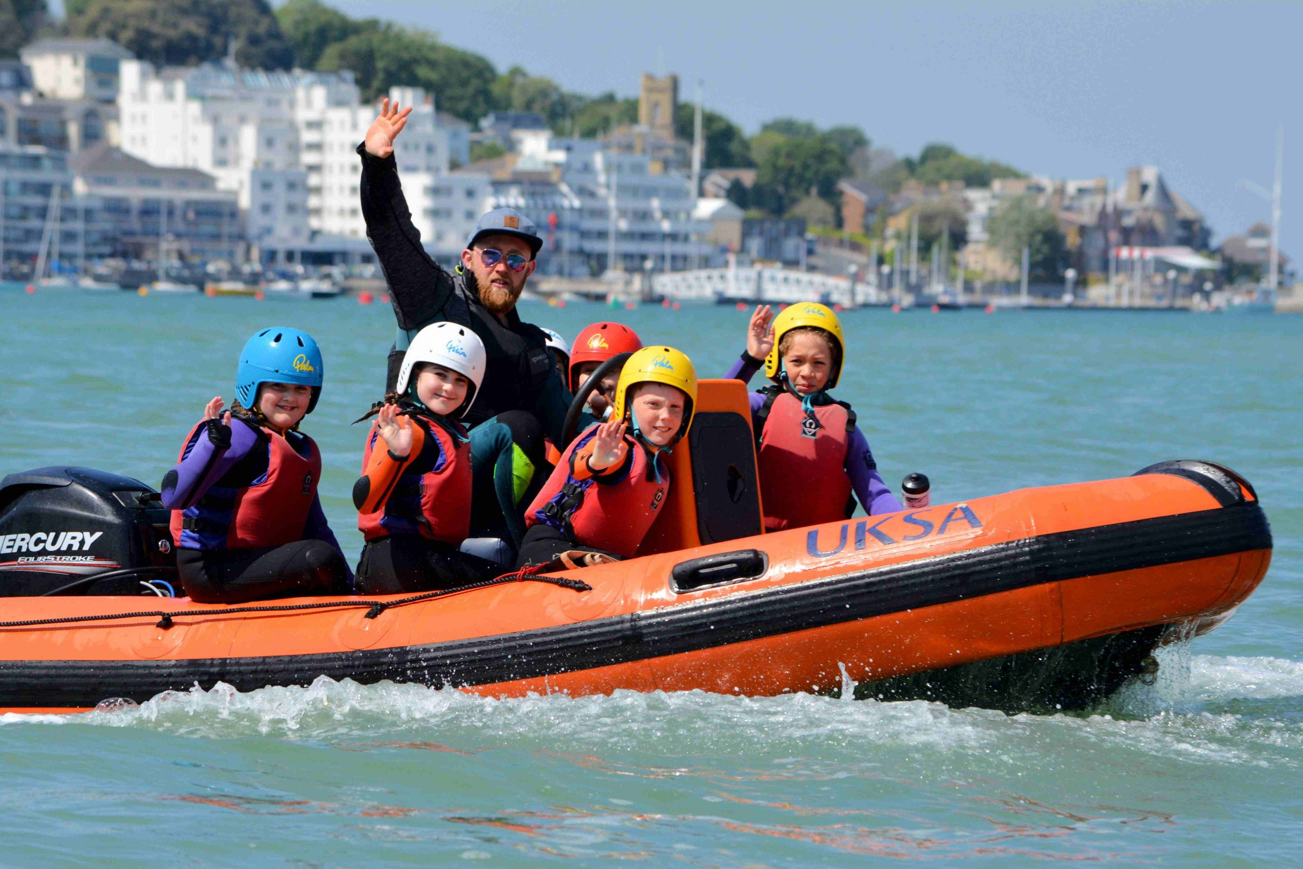 Children and UKSA instructor waving on a powerboat