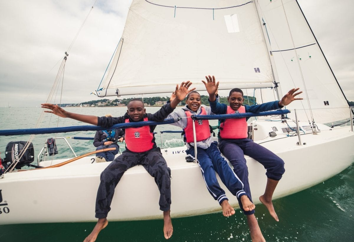 Three young males waving whilst onboard a keelboat