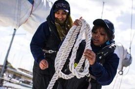 Two female yachting students holding rope