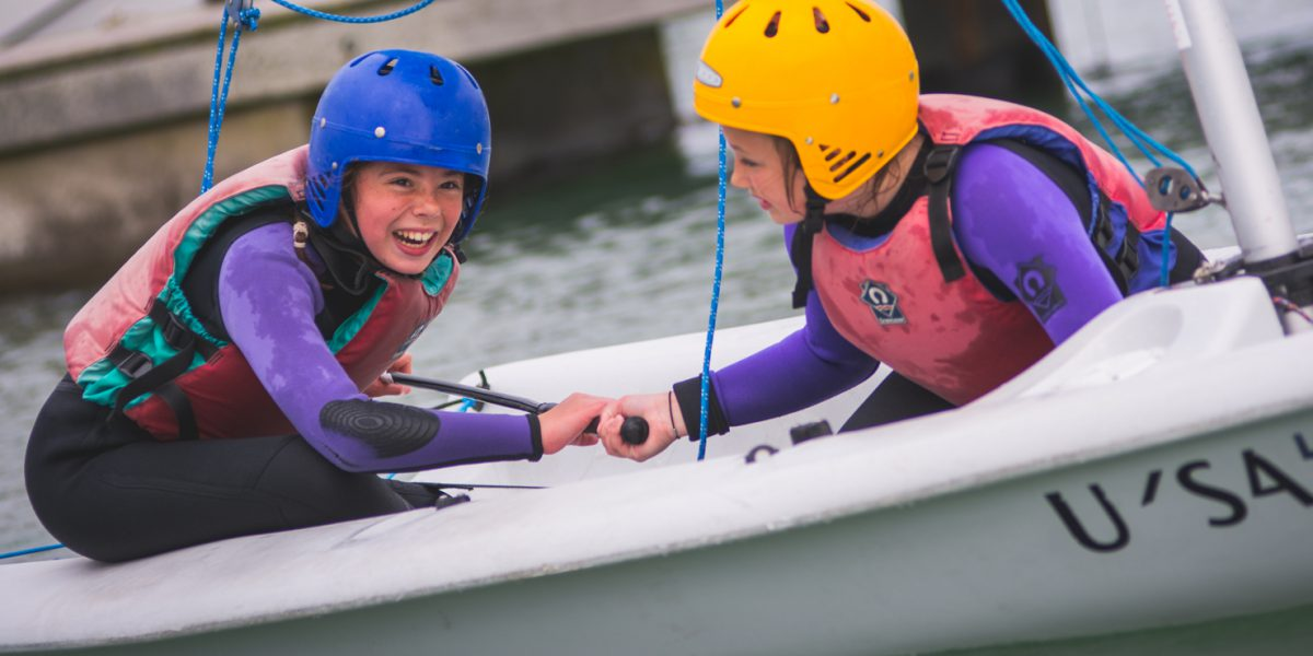 Two young female children navigating a dinghy
