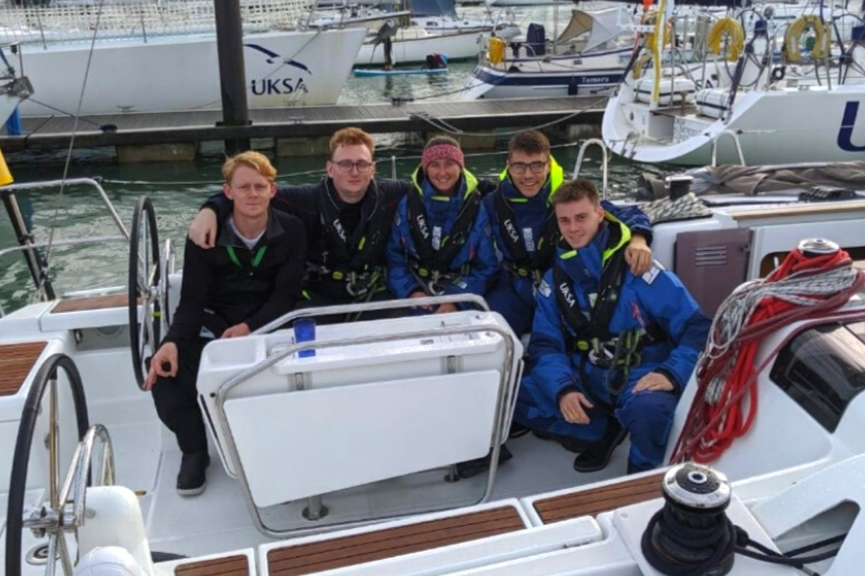A group of students posing for the camera onboard a yacht