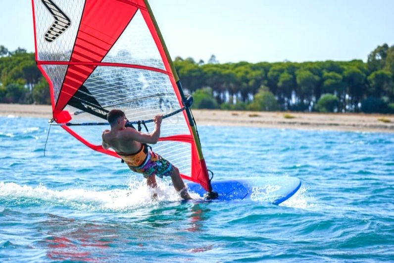 A young male windsurfing