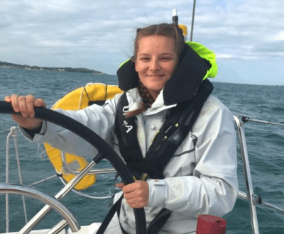Katie Sewell at the wheel of a yacht