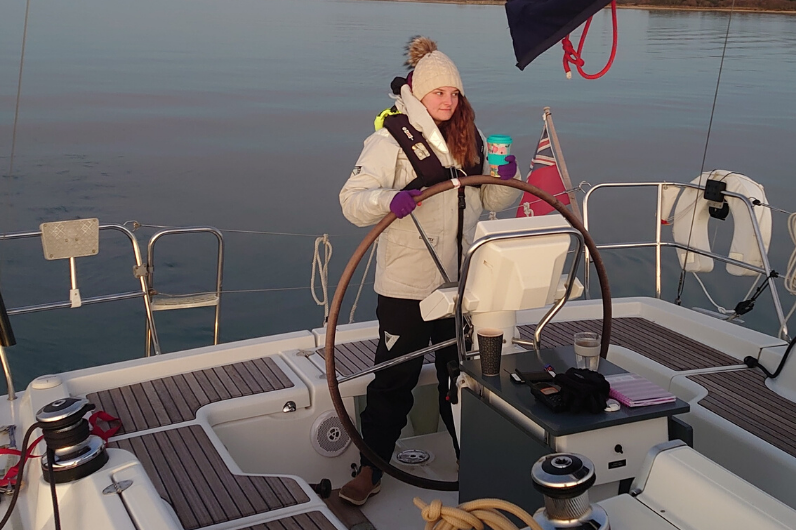Katie Sewell at the helm of a yacht