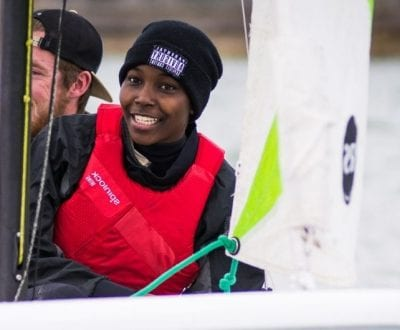 A smiling young person on a dinghy