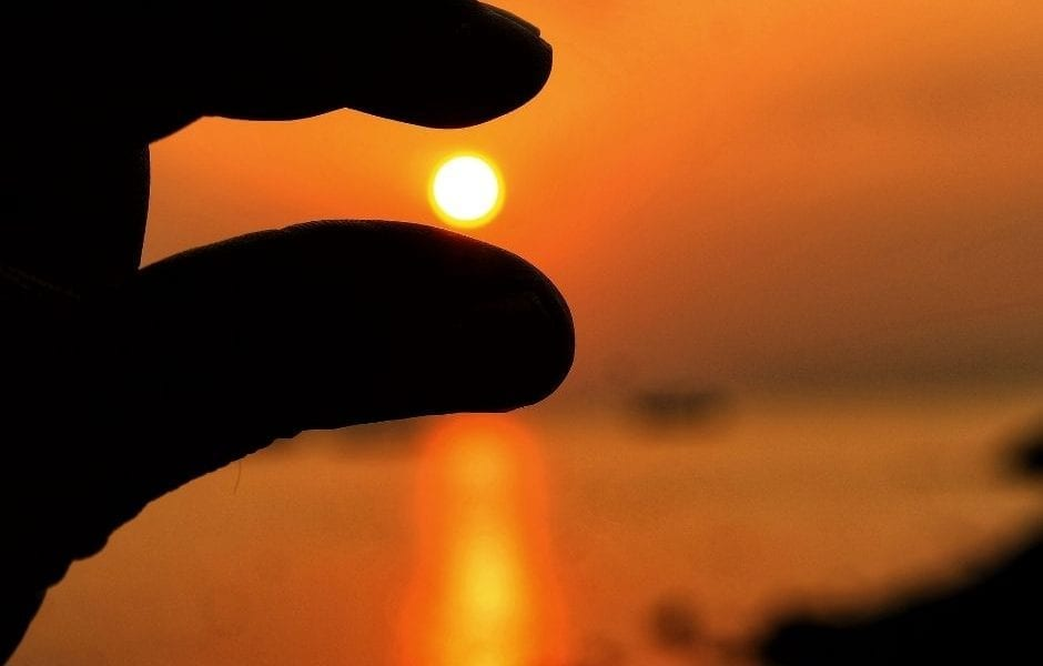 A hand pinching the sun