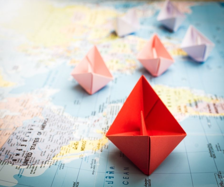 A red paper ship on a map
