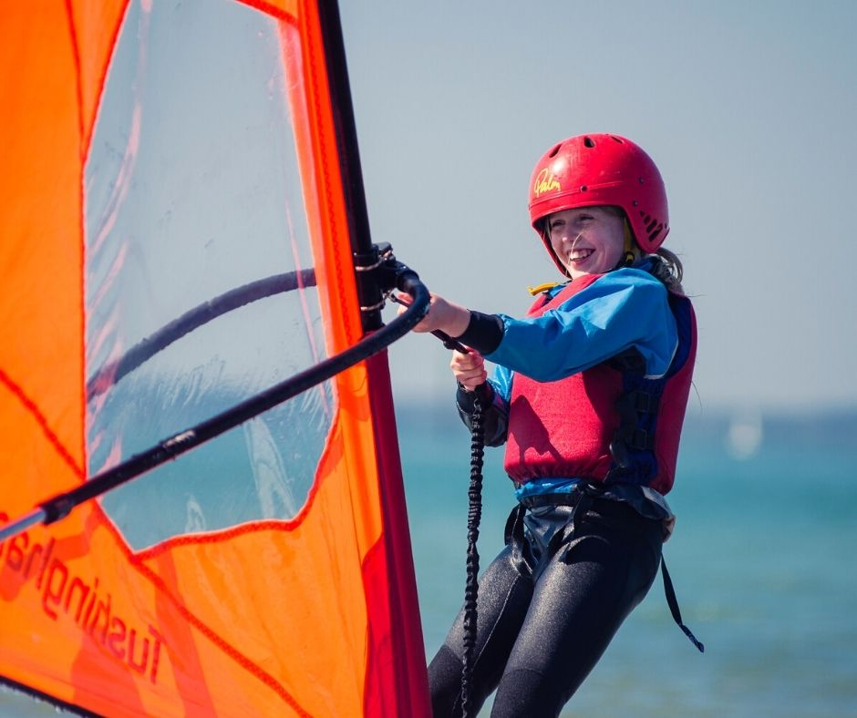 A young girl smiling while wind surfing